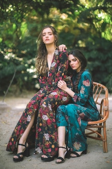 Vrouw poseren in gebloemde jurken en hoge hakken
