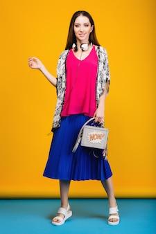 Vrouw poseren in stijlvolle zomer mode en kleurrijke sfeer tas