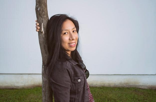 Vrouw poseren leunend op een boom in de straat
