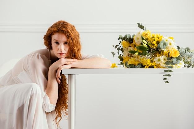 Vrouw poseren met boeket van lentebloemen op tafel