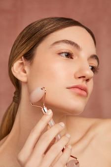 Vrouw poseren met roze gezicht tool close-up