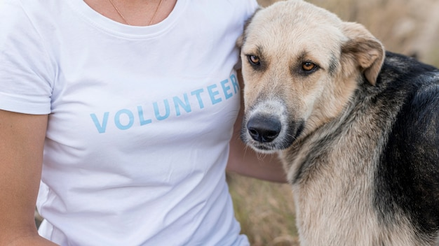 Vrouw poseren met schattige maar droevige hond buitenshuis