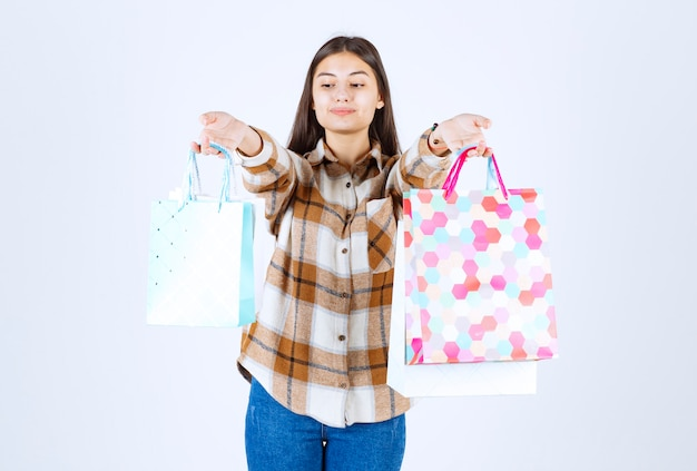 Vrouw poseren met stelletje boodschappentassen over witte muur.