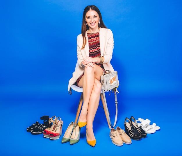 Vrouw poseren met stijlvolle schoenen zomer mode en tas, lange benen, winkelen
