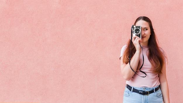 Vrouw poseren terwijl het nemen van een foto met camera