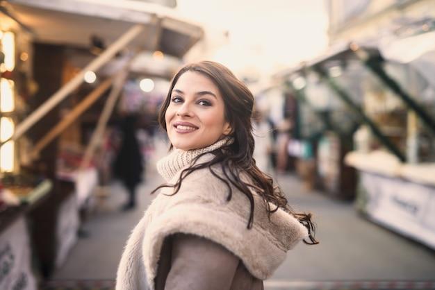 Vrouw poseren terwijl ze op straat staat. kerst vakantie concept.