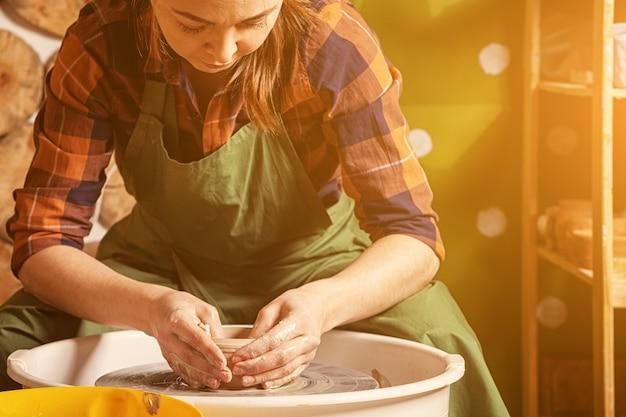 Vrouw pottenbakker beeldhouwt een klei