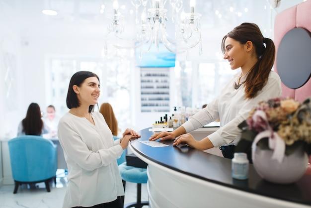 Vrouw praat met beheerder van schoonheidssalon.