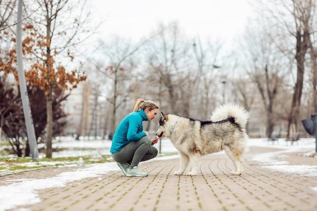 Vrouw praat met haar hond terwijl ze op besneeuwde winterdag in het openbaar park hurkt. huisdieren, weekendactiviteiten, winter, sneeuw, vriendschap, honden