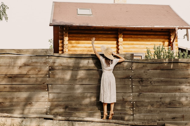 Vrouw praat over een houten hek met haar buren