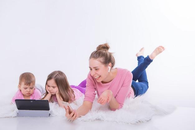 Vrouw praat over telefoon via hoofdtelefoon en kinderen kijken cartoon op tablet