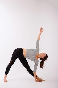 Vrouw praktijken yoga witte geïsoleerde achtergrond. yoga dag. gezond lichaam