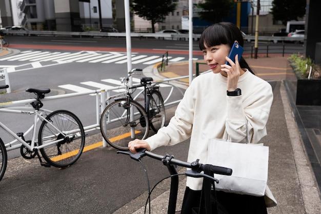 Vrouw praten aan de telefoon en het gebruik van elektrische fiets in de stad