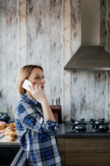 Vrouw praten aan de telefoon in de keuken