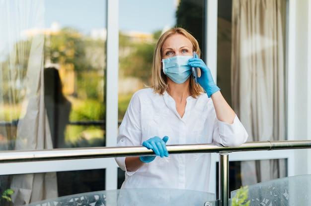 Vrouw praten aan de telefoon thuis met medische masker en handschoenen