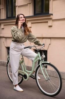Vrouw praten aan de telefoon tijdens het fietsen