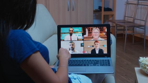 Vrouw praten met mensen uit het bedrijfsleven op webcam. externe werknemer die online vergadert, videoconferentie overlegt met collega's tijdens een videogesprek dat thuis achter een laptop op de bank ligt