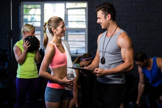 Vrouw praten met trainer in de sportschool