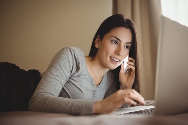 Vrouw praten op mobiele telefoon tijdens het gebruik van laptop