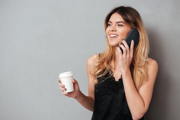 Vrouw praten over de telefoon tijdens het drinken om te gaan koffiekopje