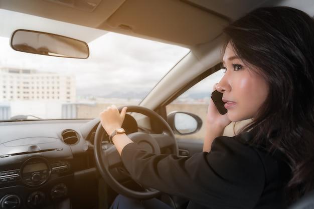 Vrouw praten over de telefoon tijdens het rijden