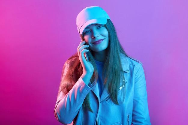 Vrouw praten over mobiel terwijl ze tegen roze neon muur staat