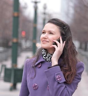 Vrouw praten over smartphone in stad straat.