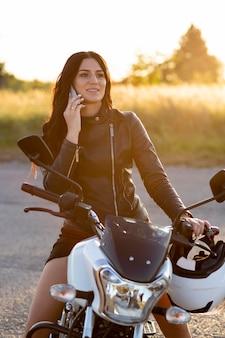 Vrouw praten over smartphone zittend op haar motorfiets