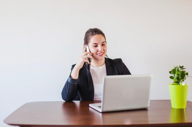 Vrouw praten telefoon op laptop