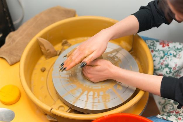 Vrouw probeert een nieuwe hobby zoals pottenbakken op het wiel.