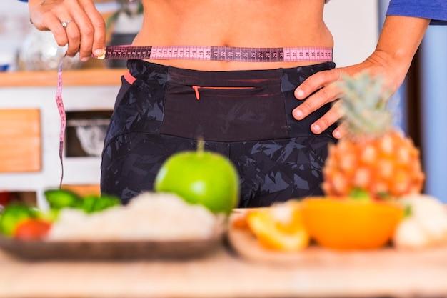Vrouw probeert gezond en gezond te eten - meterlijn - op de tafel liggen veel groenten en fruit