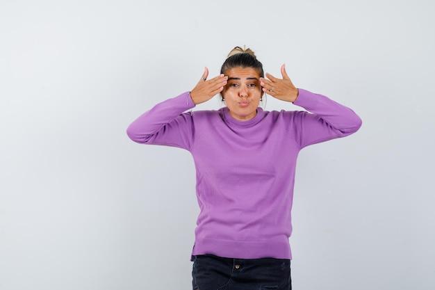 Vrouw probeert ogen te bedekken met handen in wollen blouse en kijkt aarzelend