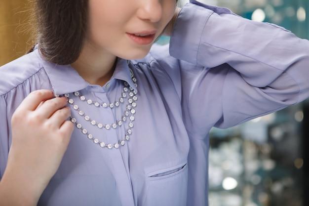 Vrouw probeert op een diamanten halsketting