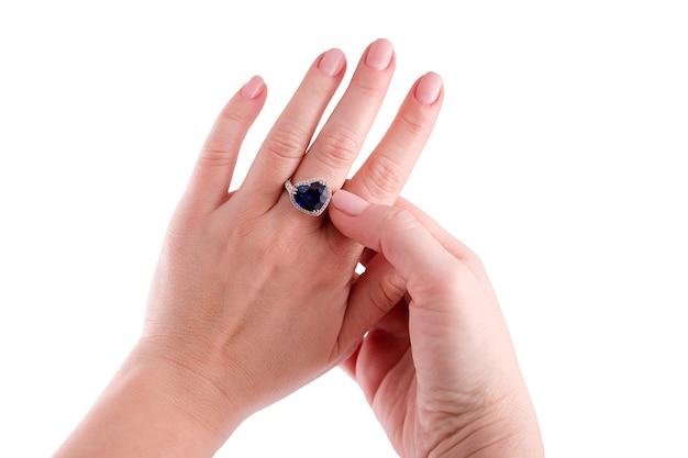 Vrouw probeert op een hartvormige blauwe saffier kostbare ring geïsoleerd op een witte achtergrond