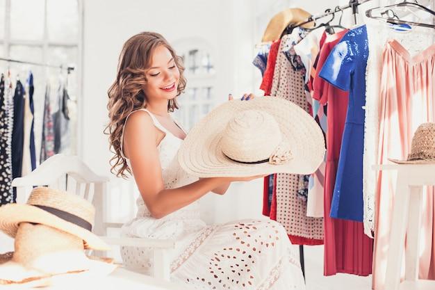 Vrouw probeert op een hoed. gelukkig zomer winkelen.