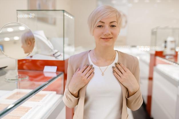 Vrouw probeert op gouden ketting bij de showcase in juwelier. vrouwelijke persoon die gouden decoratie in juwelenwinkel koopt