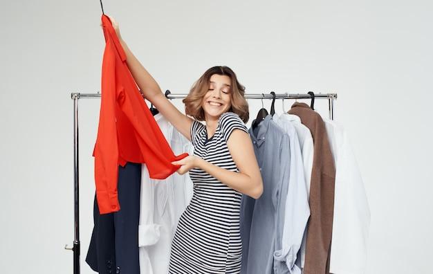 Vrouw probeert op modieuze kleding in een winkel stijl overhemd.