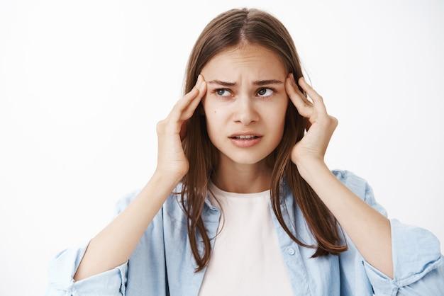 Vrouw probeert te denken en te handelen in een moeilijke situatie met vingers op de slapen, fronsend opzij te staren, gebrek aan concentratie, wil focus maar lijdt aan hoofdpijn