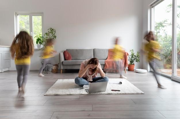 Vrouw probeert thuis op laptop te werken terwijl haar kinderen rondrennen