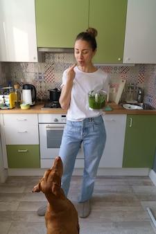 Vrouw proeft met haar vinger aromatische pestosaus opgeklopt in blender vyzsla hond bedelend om eten