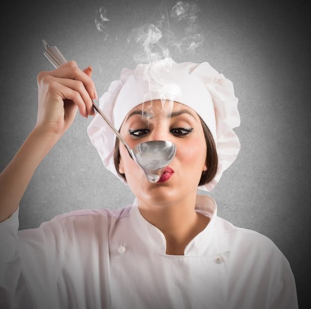 Vrouw proeverij chef proeft een dampende pollepel