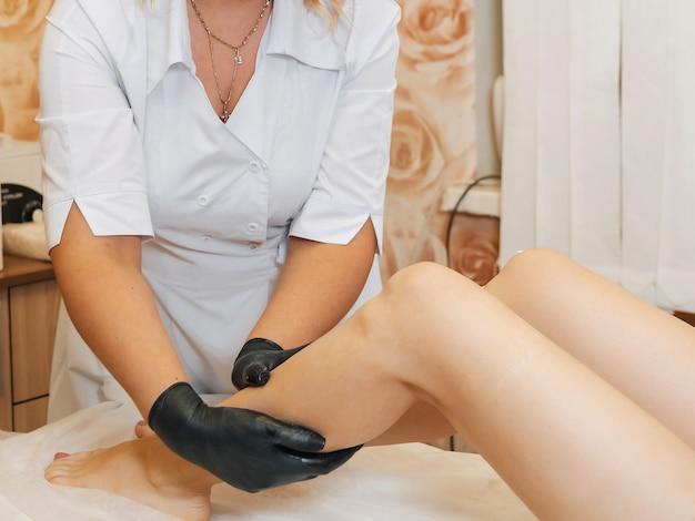 Vrouw professionele schoonheidsspecialiste en masseur zorgt voor de voeten van de meisje-client