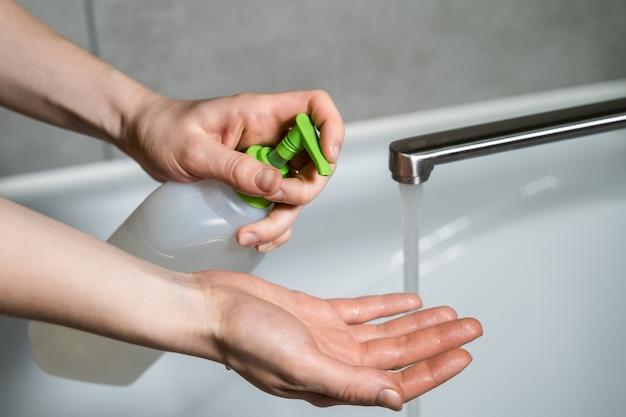 Vrouw push dispenser en vloeibare zeep uit de hand geperst. vrouwelijke handen knijpen vloeibare zeep uit de dispenser. was je handen. coronavirus- of covid19-preventie.