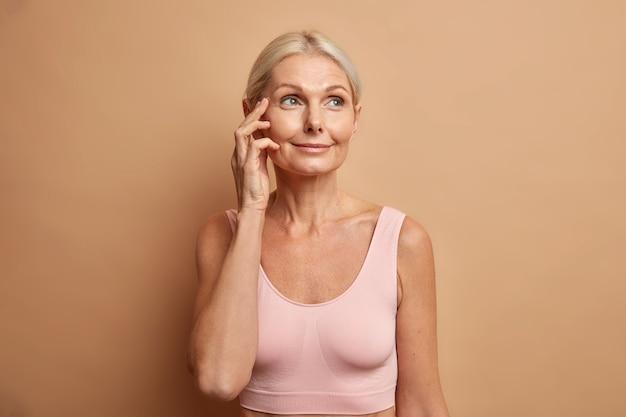 Vrouw raakt gezicht heeft gezonde huid na cosmetische ingrepen of gezichtsbehandelingen