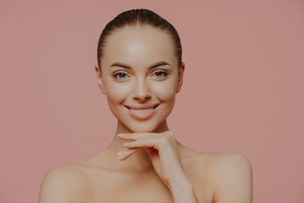 Vrouw raakt kin zachtjes aan, geniet van een vlekkeloze huid na schoonheidsprocedures, poseert naakt, heeft natuurlijke make-up, geïsoleerd op roze
