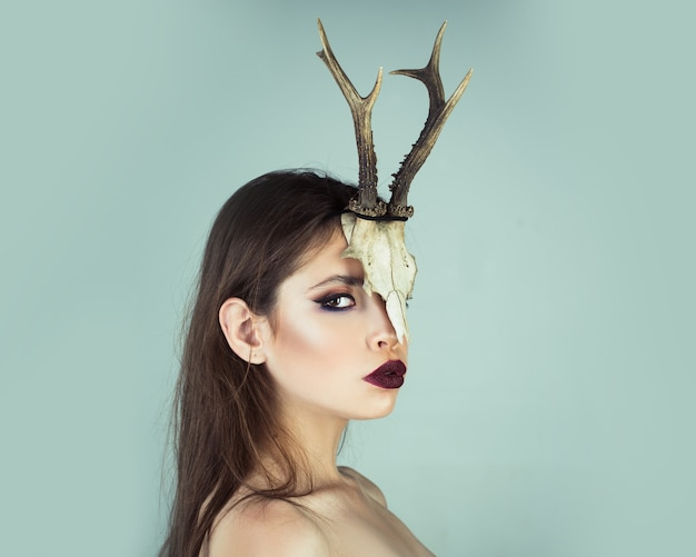 Vrouw ram in dierlijke schedel hoorns. jonge heks. vrouw heks, halloween. schoonheid van vrouw met dierlijke schedel en geweien.