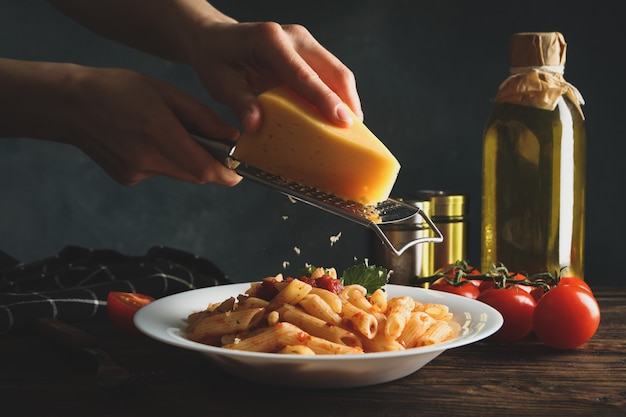 Vrouw raspen kaas op pasta. pasta samenstelling koken