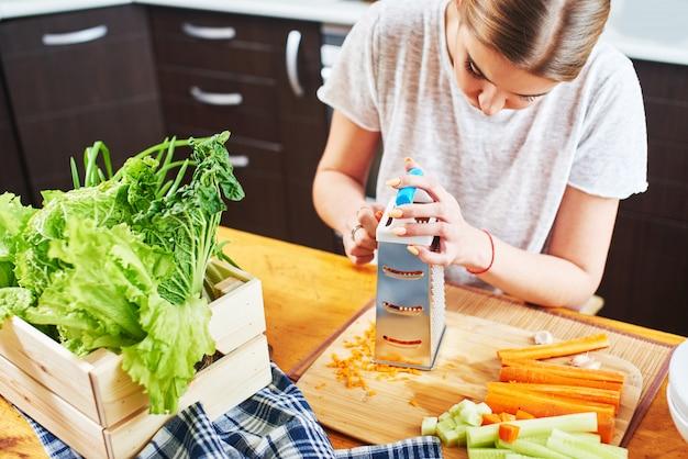 Vrouw raspt de wortelen in de keuken