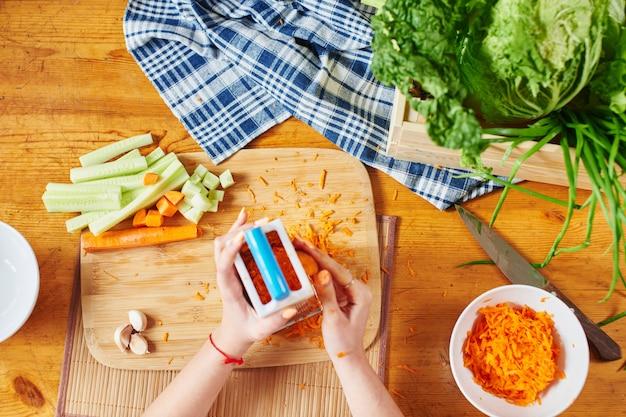 Vrouw raspt de wortelen op een houten bord