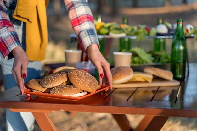 Vrouw regelen van voedsel op tafel voor vrienden om mee te doen